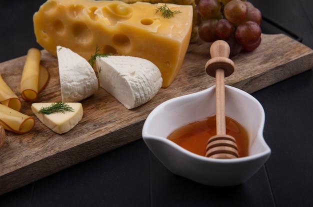 Vue latérale type de fromage sur un support avec des raisins et du miel sur fond noir