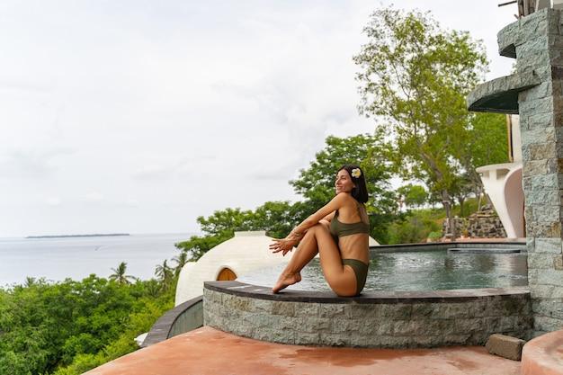 Vue latérale d'un vacancier bronzé souriant assis au bord d'une piscine