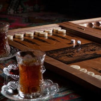 Vue latérale verre de thé avec backgammon et confiture sur table de tapis
