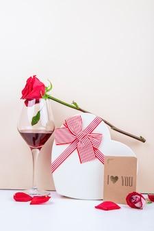 Vue latérale d'un verre de vin rouge couleur rose et une boîte cadeau en forme de coeur à égalité avec un arc avec une petite carte postale sur fond blanc