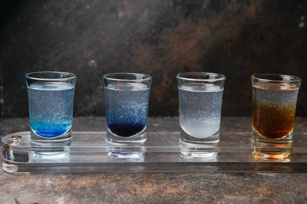 Vue latérale verres à liqueur avec des boissons de couleur sur un verre
