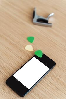Vue latérale verticale de l'écran du smartphone avec un contenu vierge. étudier et apprendre le concept en ligne de leçons de guitare. explorez la musique et la technologie ensemble. médiators et pont au téléphone à écran blanc.
