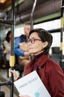 Vue latérale verticale portrait d'une femme mûre élégante en bus voyageant en transports en commun en ville