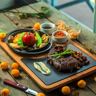 Vue latérale de la viande de boeuf grillée servie avec légumes et sauce sur planche de bois