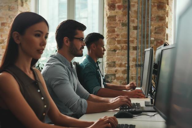 Vue latérale de la vie de bureau de jeunes employés travaillant sur des ordinateurs assis dans un espace ouvert moderne