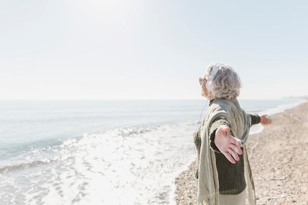 Vue latérale vieille femme sur la plage