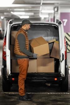 Vue latérale de la voiture de chargement de l'homme avec des paquets