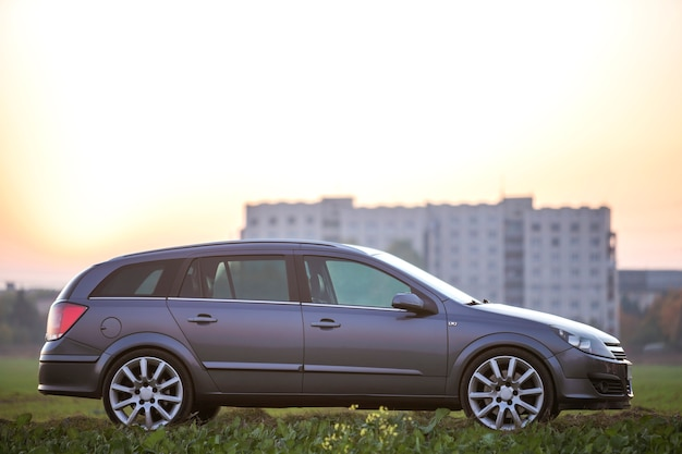Vue latérale d'une voiture vide en argent gris garée dans la campagne sur un paysage rural flou et un ciel clair orange vif au fond de l'espace de copie au coucher du soleil. transport, voyage, concept de conception de véhicules.