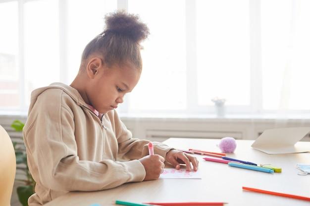 Vue latérale vue portrait d'une jolie fille afro-américaine signant une carte faite à la main comme cadeau pour la fête des pères, espace pour copie