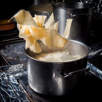 Vue latérale xengel avec marmite et eau bouillante et papier d'aluminium dans le poêle