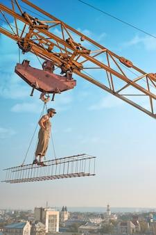 Vue de loin du constructeur athlétique en vêtements de travail debout sur la construction en haut. grue de construction tenant la construction avec l'homme au-dessus de la ville. construction extrême de maison dans la grande ville. homme regardant vers le bas.