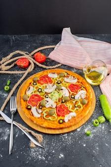 Vue lointaine avant savoureuse pizza aux champignons avec tomates, olives vertes et champignons avec tomates fraîches