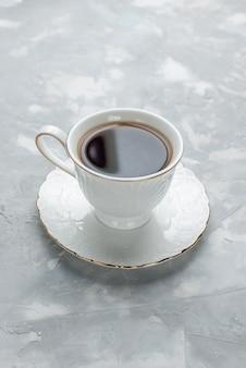 Vue lointaine avant tasse de thé chaud à l'intérieur tasse blanche sur plaque de verre sur un bureau léger