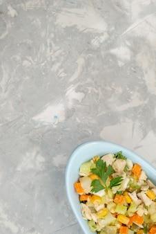 Vue lointaine du haut de la salade de légumes en tranches à l'intérieur de la plaque bleue sur le fond clair repas de salade de légumes