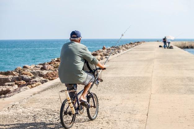 Vue d'un long jet d'eau avec un pêcheur à vélo qui se déplace.