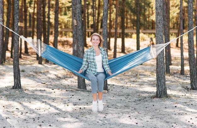 Vue longue femme assise dans un hamac
