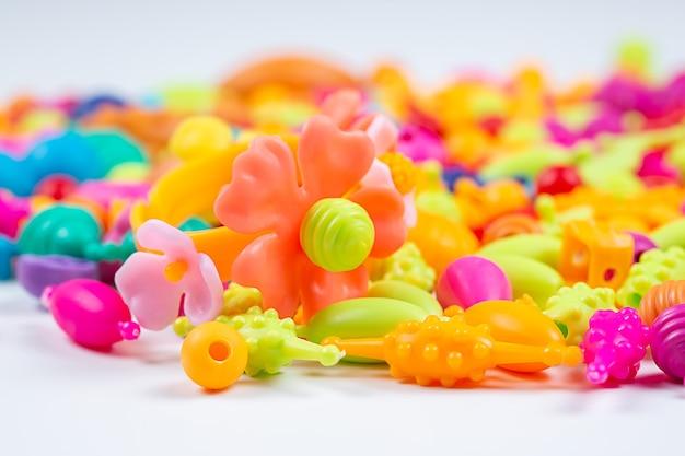 Vue macro de perles pour la créativité des enfants, vous pouvez faire des bracelets, des colliers et des bagues sur fond blanc