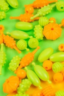 Vue macro de perles pour la créativité des enfants, vous pouvez faire des bracelets, des colliers et des bagues sur fond vert