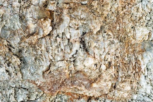 Vue macro de la surface de la pierre de couleur grise, brune et blanche. fond de nature détaillée ou texture de motif prise dans un environnement naturel. altéré au fil des ans, effet unique et inimitable au design texturé.