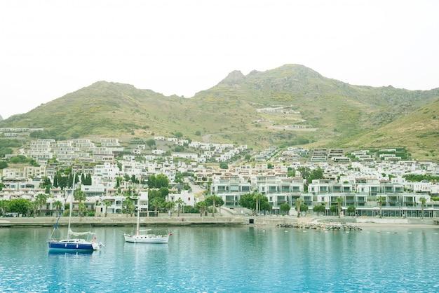 Vue sur la magnifique mer, la ville et un bateau de pêche à turgutreis bodrum