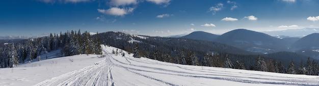 Vue sur le magnifique panorama hivernal des pentes enneigées et des collines parmi les nuages blancs luxuriants