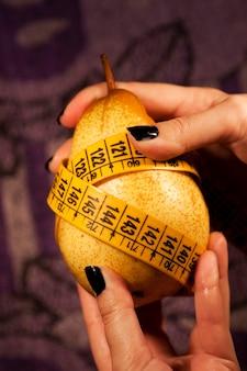 Vue d'une main de femme saisissant une poire avec un ruban à mesurer.