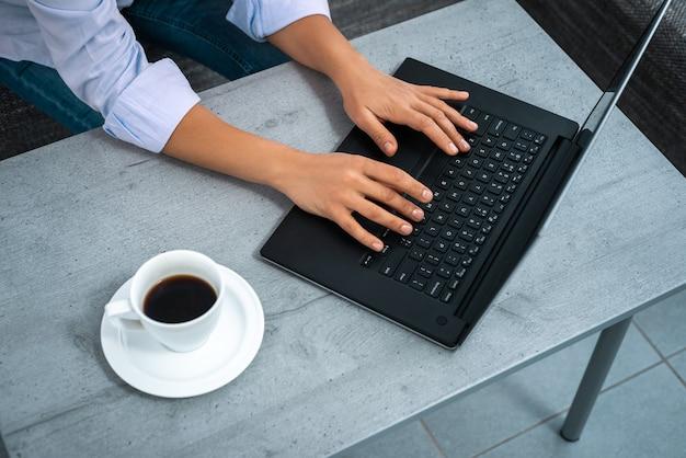 La vue des mains d'une femme tapant sur un ordinateur portable. travail à distance de la maison.