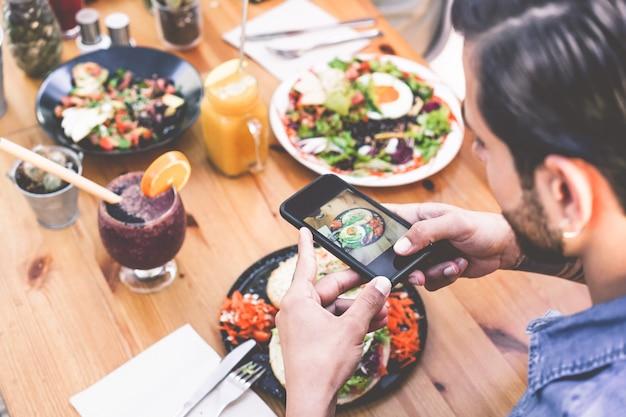 Vue des mains de l'homme d'influence mangeant le brunch tout en faisant la vidéo du plat avec le téléphone portable dans le restaurant bar branché