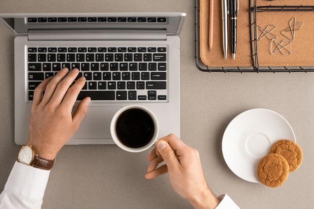 Vue des mains de jeune gestionnaire de bureau occupé ou courtier avec une tasse de café en prenant un verre et en touchant les touches du clavier d'ordinateur portable le matin
