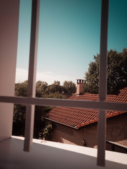 Vue sur la maison et les arbres à travers la fenêtre