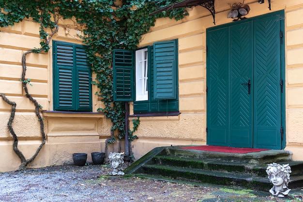 Vue de la maison jaune qui est recouverte de raisins sauvages.