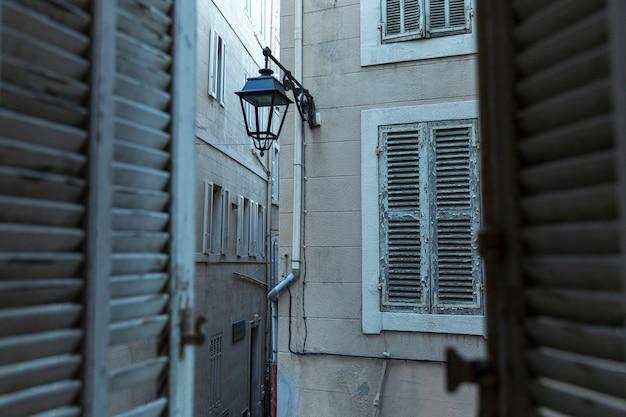 Vue des maisons de la vieille ville depuis une fenêtre aux volets en bois. fermer.