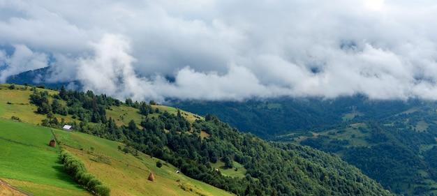 Vue majestueuse sur de belles montagnes de brouillard et de nuages dans un paysage de brume. l'heure d'été après la pluie