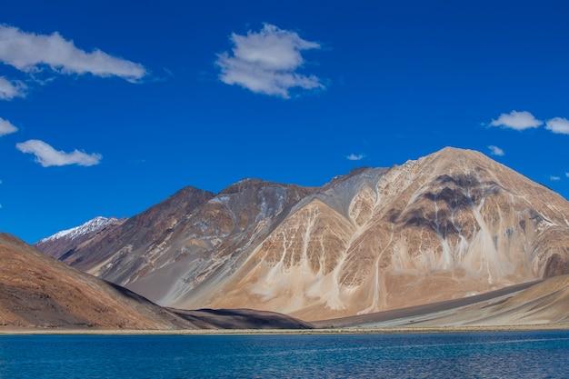Vue sur les majestueuses montagnes rocheuses contre le ciel bleu et le lac pangong dans l'himalaya indien, région du ladakh, jammu-et-cachemire, inde. concept de nature et de voyage