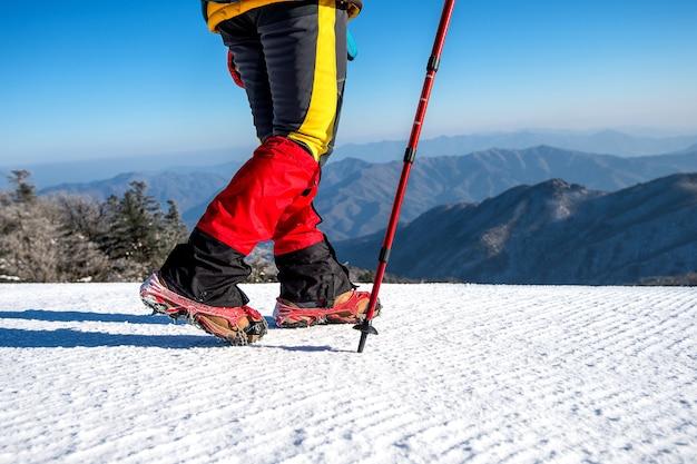 Vue de la marche sur la neige avec des raquettes et des pointes de chaussures en hiver
