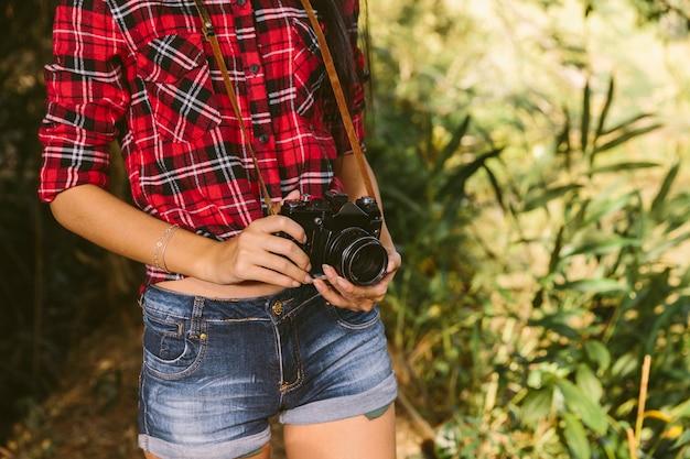 Vue de médiane d'une femme tenant un appareil photo
