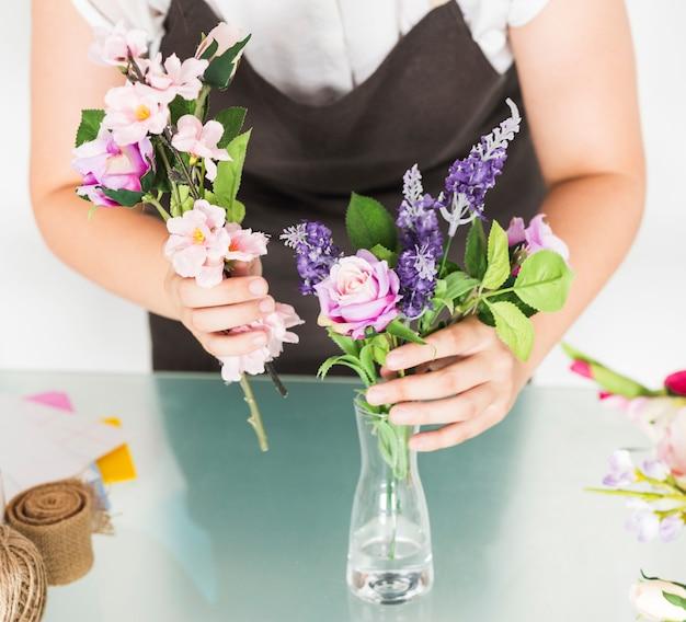 Vue médiane de la main d'une femme mettant des fleurs dans un vase sur un bureau en verre