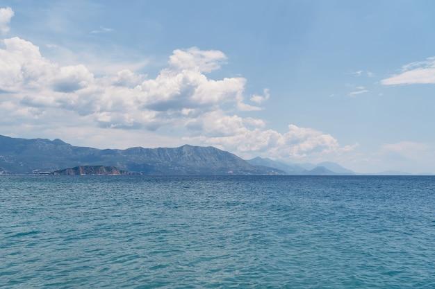 Vue de la mer aux montagnes et à l'île sur fond de ciel bleu