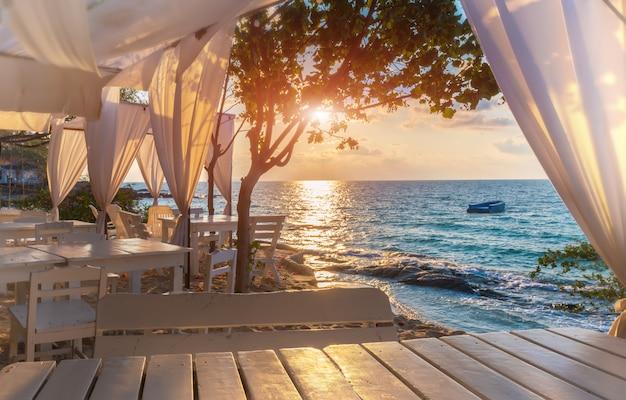 Vue sur la mer bleue de l'île avec une décoration blanche, lieu de détente éclairé au lever du soleil.