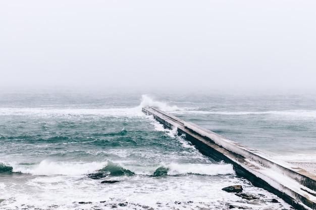 Vue sur la mer et une jetée gelée en hiver lors d'une chute de neige
