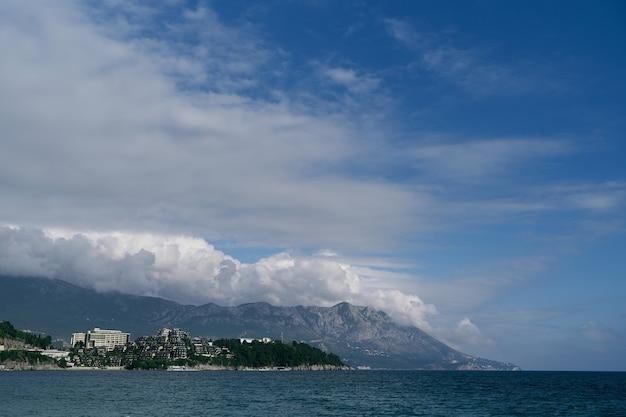 Vue de la mer à la plage abrite des arbres et des montagnes budva monténégro