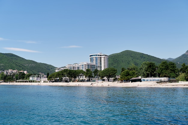 Vue de la mer à la plage et à l'hôtel parmi la verdure dans les montagnes budva monténégro