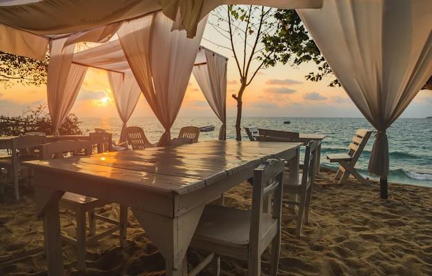 Vue mer avec table design blanche et tissu avec éclairage au lever du soleil.
