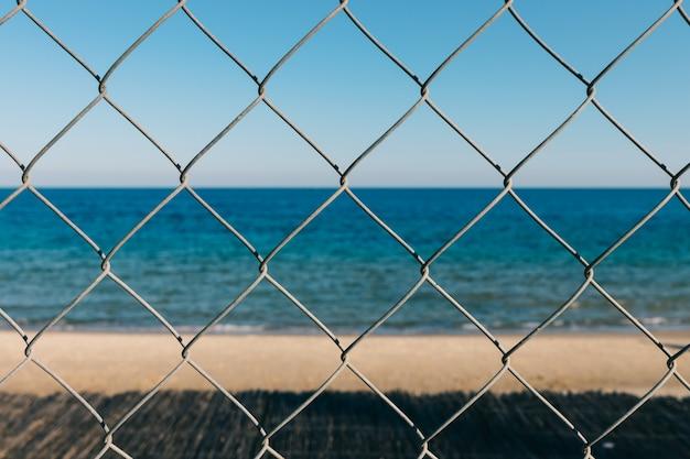 Vue sur la mer à travers la grille métallique