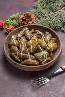 Vue à mi-hauteur d'un plat de viande dolma à feuilles savoureuses à l'intérieur d'une assiette brune sur un espace sombre