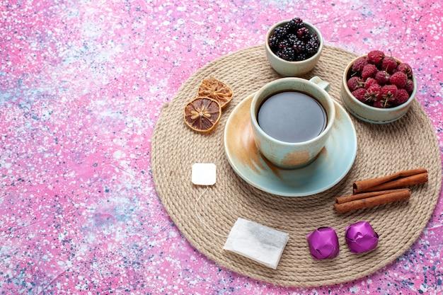 Vue de la moitié des baies fraîches framboises et mûres avec du thé et de la cannelle sur le bureau rose.