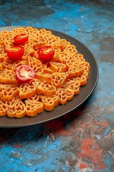 Vue de la moitié inférieure des coeurs de pâtes italiennes coupées de tomates cerises sur une plaque ovale noire sur une surface bleue