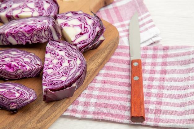 Vue de la moitié inférieure du chou rouge haché sur un couteau de planche à découper sur un torchon à carreaux rose et blanc sur une table grise
