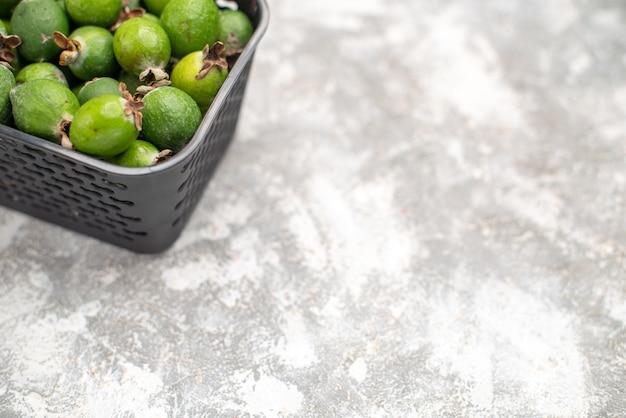 Vue de la moitié inférieure des feykhoas frais dans un panier sur une surface grise avec espace de copie