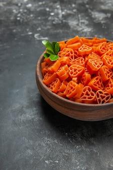 Vue de la moitié inférieure des pâtes italiennes rouges en forme de coeur dans un bol sur une surface sombre